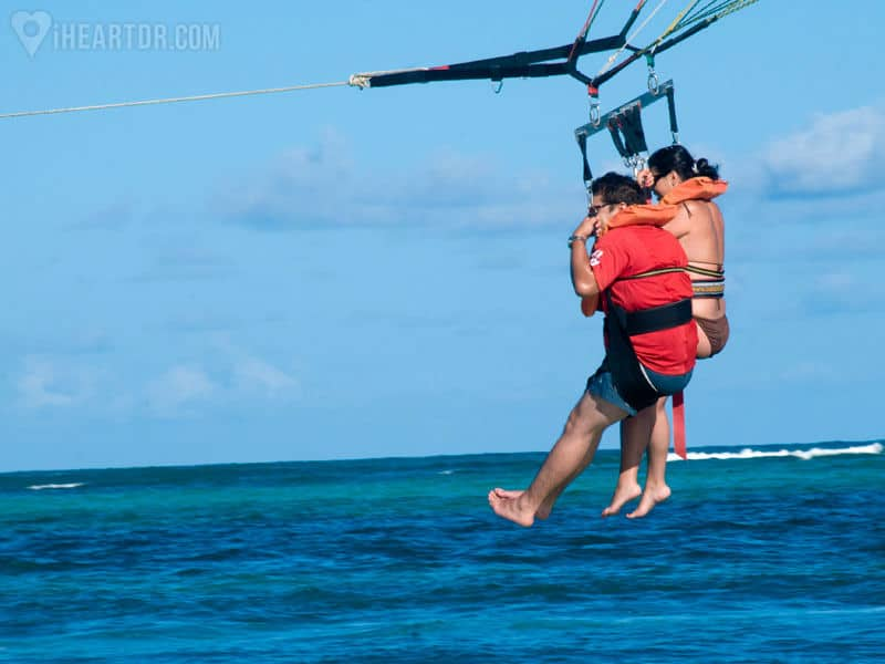 Couple parasailing about to touch the water with their feet