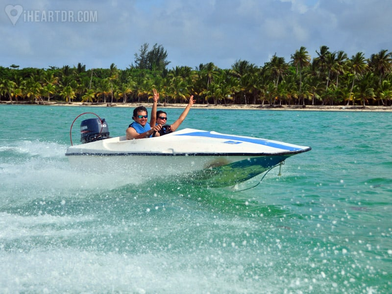 Woman with her arms up while man drives a speedboat