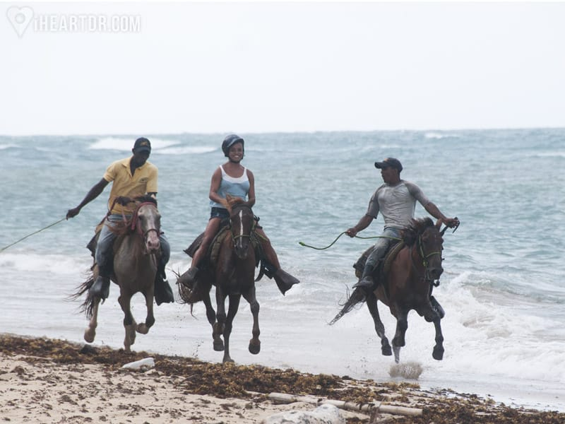 Woman and two guides galloping on their horses
