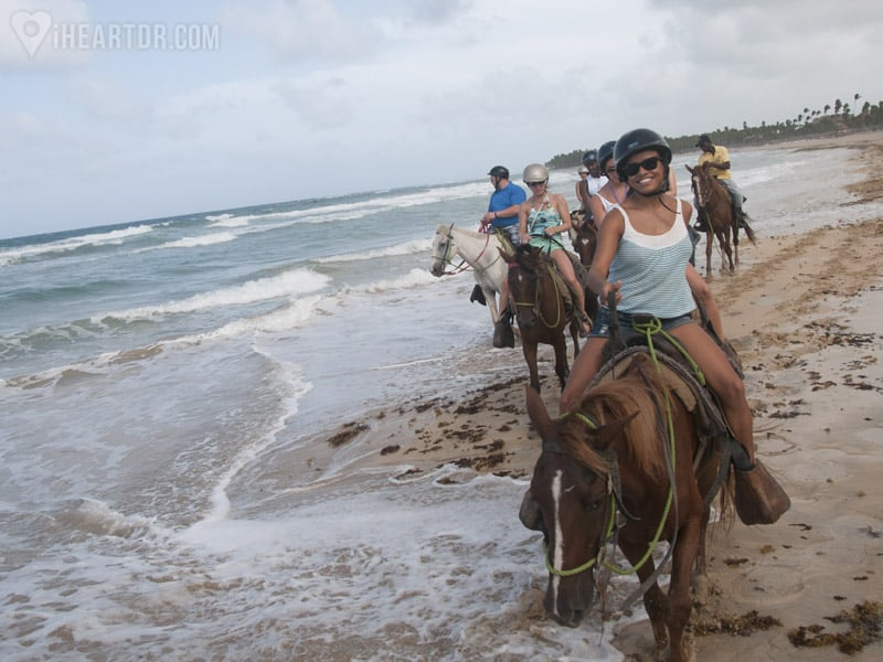 Group horseback riding on the shore