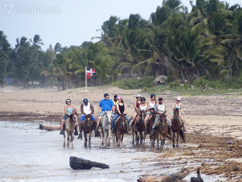 Group riding their horses on the beach with the dominican flag waving in the background