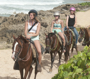 Three girls riding their horses on the beach