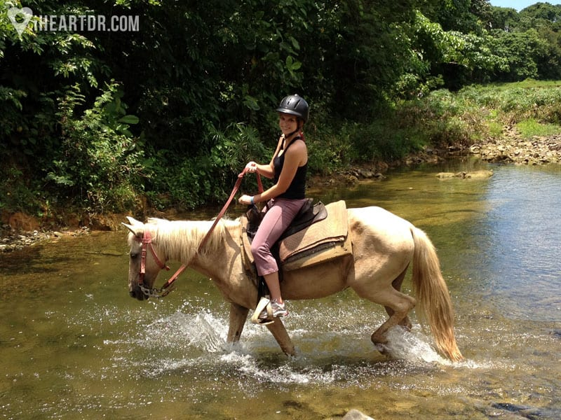 Woman riding her horse across the river
