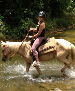 woman crossing a river on her horse