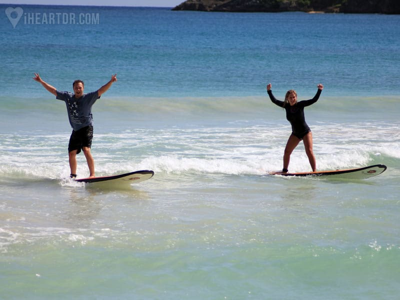 Man and woman surfing celebrating with their arms up in the air