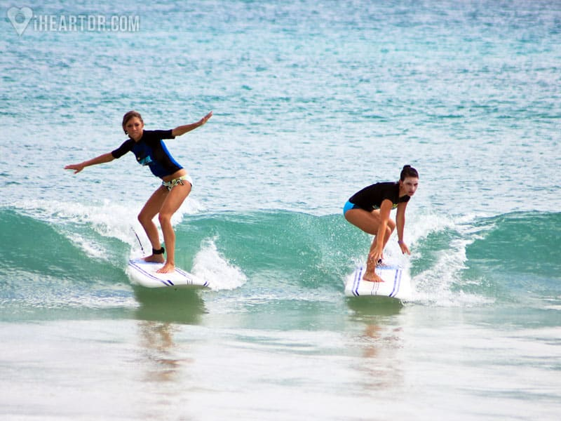 Two girls catching a wave