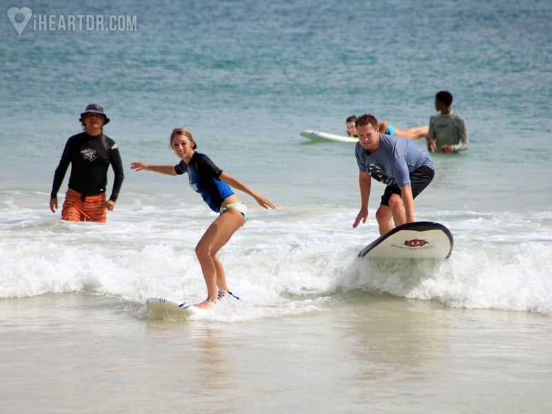 Man and woman riding a wave with instructor watching
