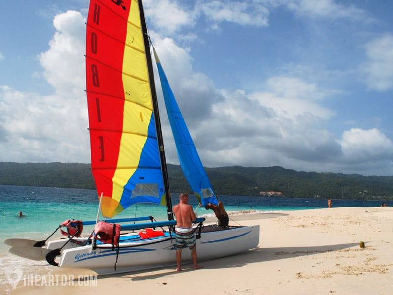Man setting up a small Catamaran on the beach