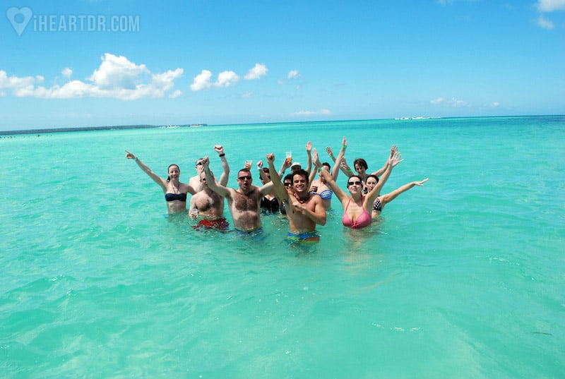 Group lifting their drinks in the air for the camera inside the water
