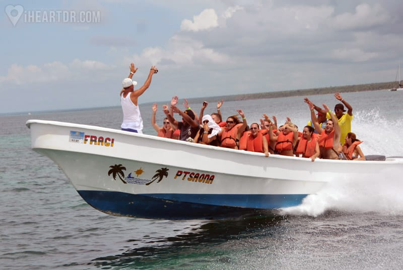 Passengers onboard a motor boat with their hands in the air