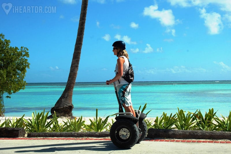Woman riding her segway with the beach as background