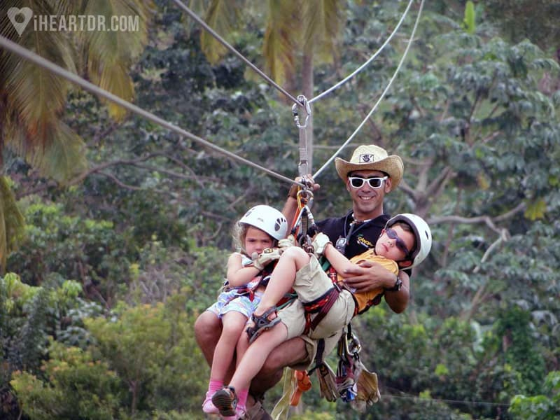 Two kids riding the zip line with one of the guides