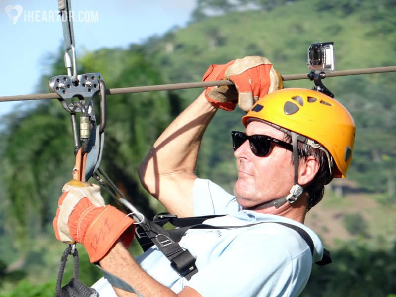 Man zip lining with a go pro camera on his helmet