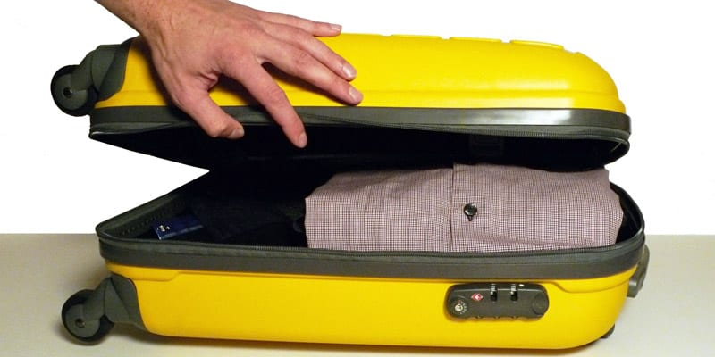Hand closing a yellow suitcase