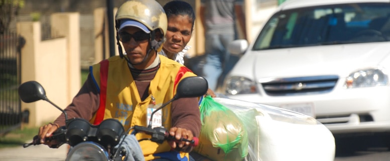 woman riding on a motorcycle taxi