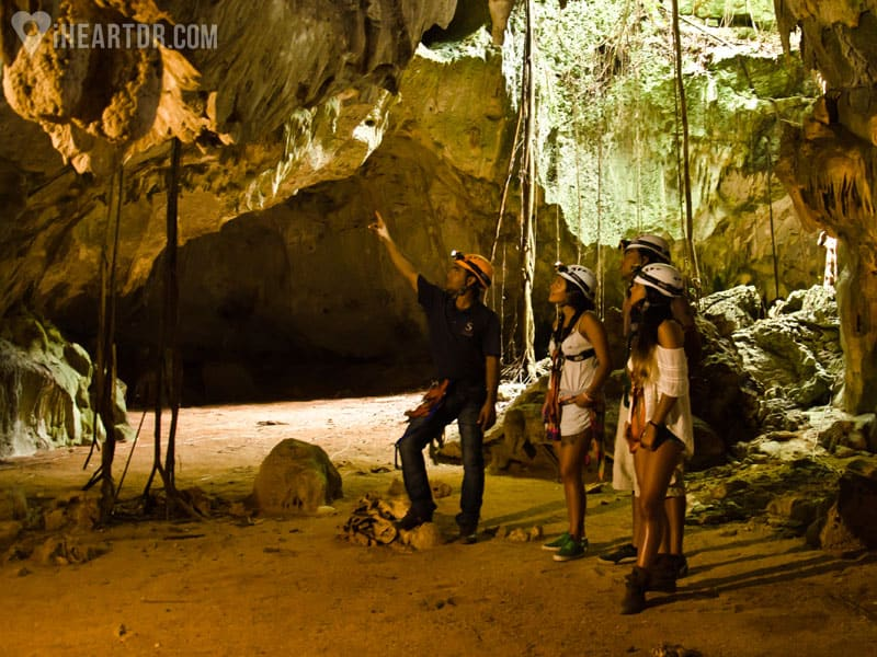 Guide explaining to a group of women information about the cave