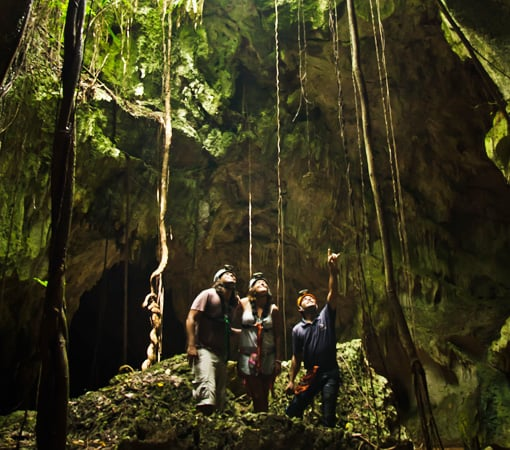 Small group looking up from the cave