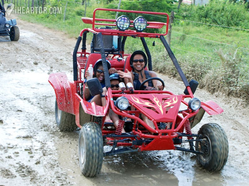 A woman and her children inside a red dune buggy