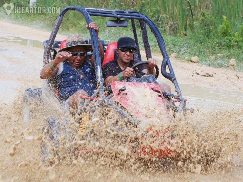 Two men driving through a puddle on a buggy