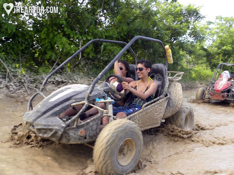 Couple driving a buggy through the mud
