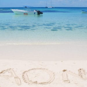 The word Saona written on the sand on the beach