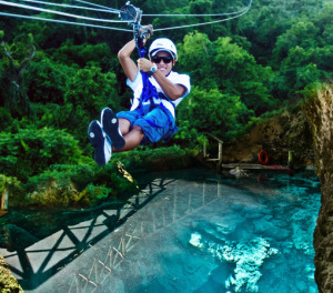 Man ziplining and the hoyo azul lagoon