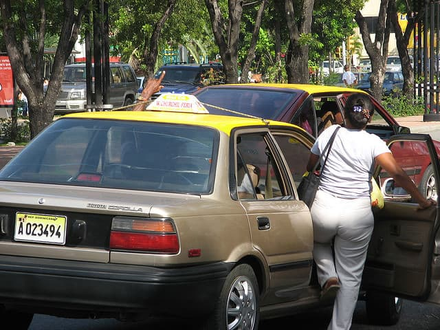 Woman boarding a carro publico in the DR