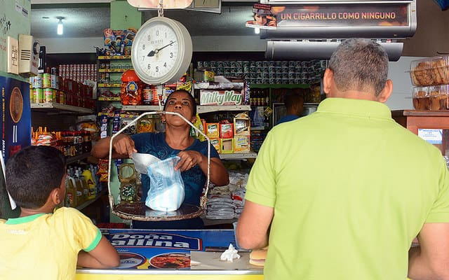 Woman selling to customers in a colmado