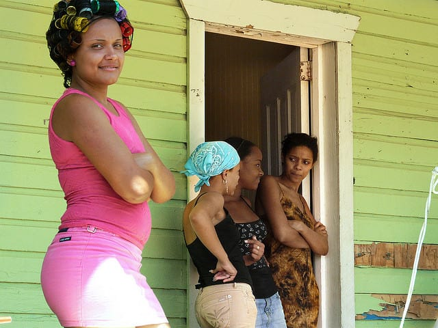 Dominican girl with hairs rolls standing in front of a house