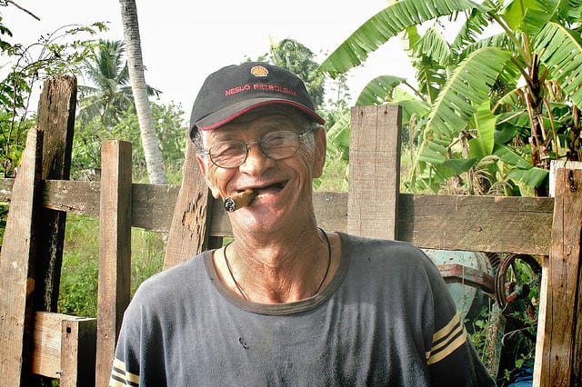Elder dominican man smiling while smoking a cogar
