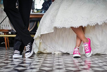 Bride and groom in informal shoes posing for picture