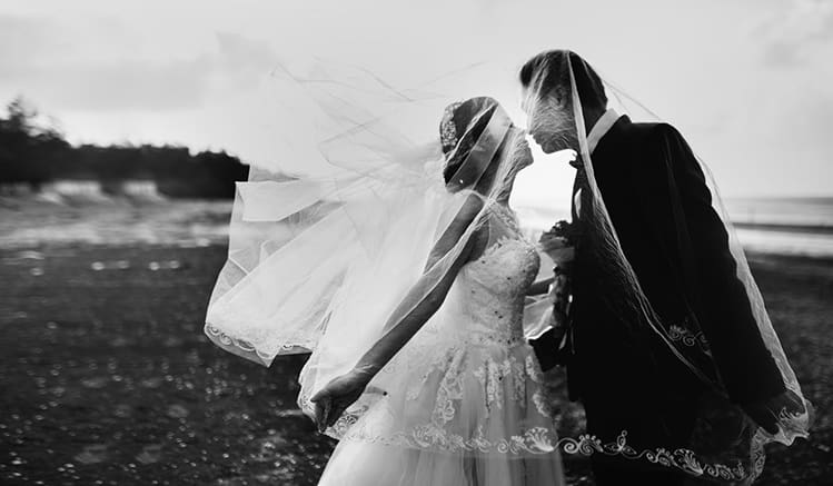 A bride and a groom kissing in black and white picture