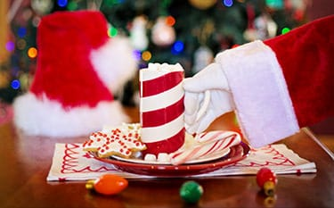 Santa Clauss' hand picking up a cup of cocoa