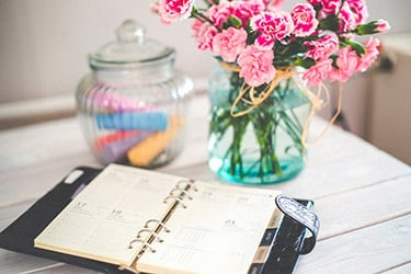 Daily planner and flowers in a table