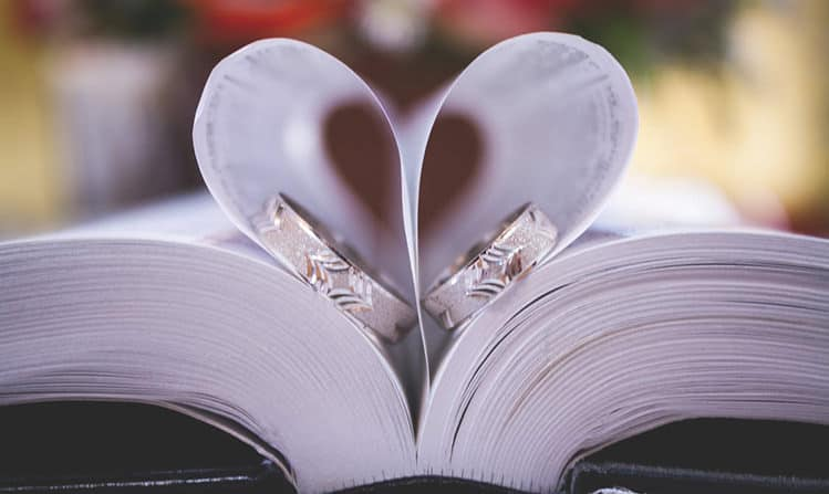 Wedding rings inside a book with the pages forming a heart