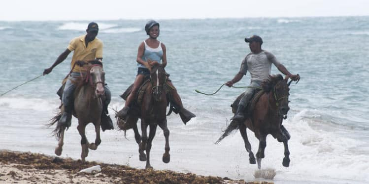 People riding horse on the beach