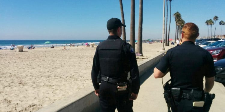 Two policemen walking in the beach