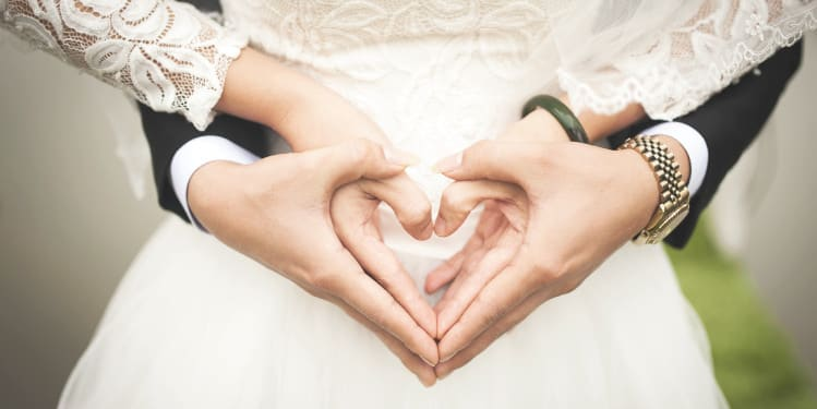 Couple making a heart sign with the hands