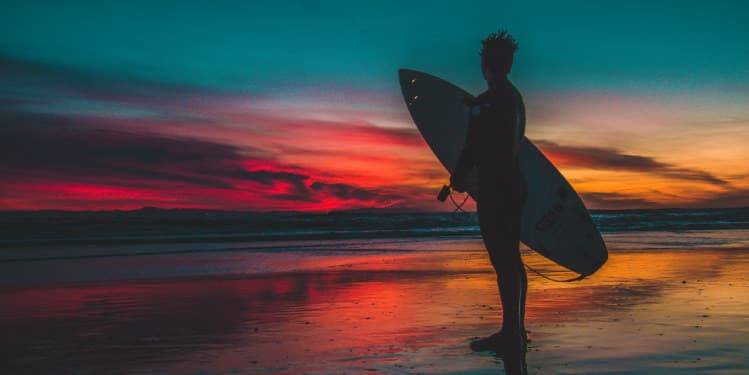 Surf woman at sunset on the beach